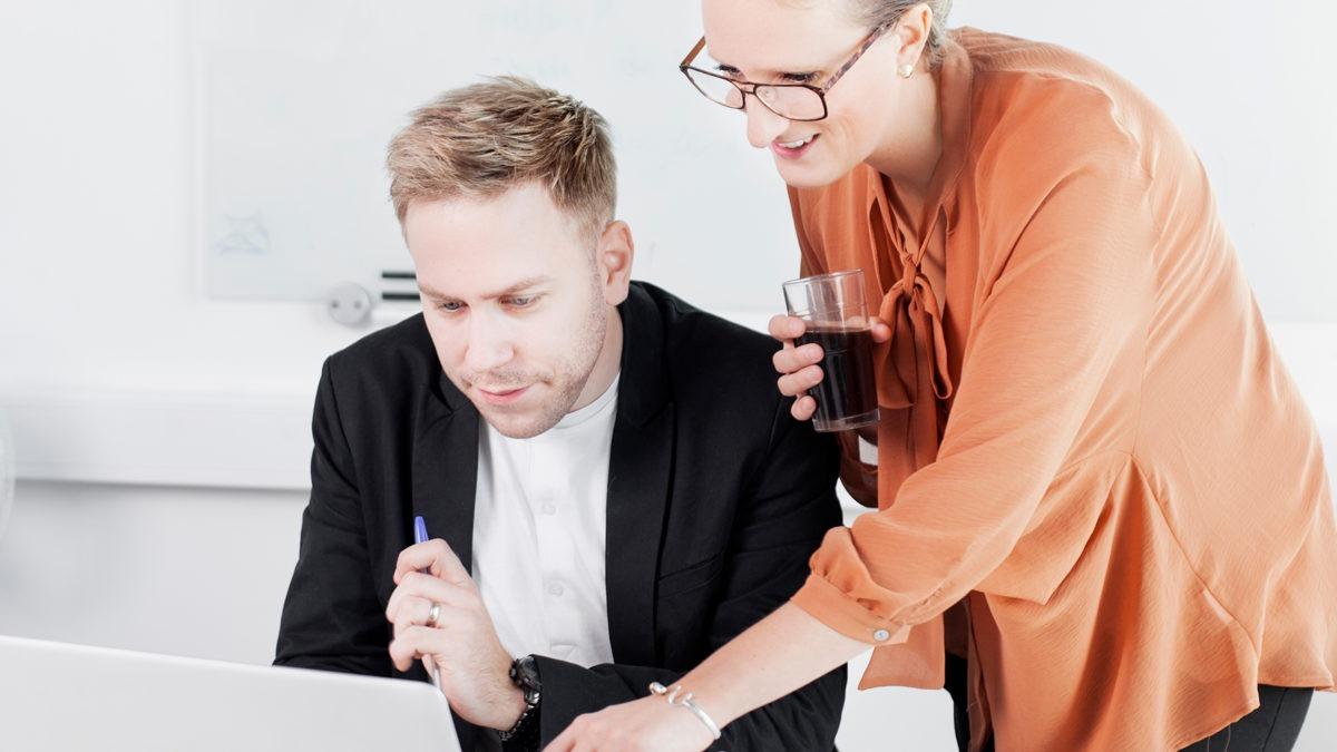 En man sitter vid en dator, bredvid honom står en kvinna i orange skjorta och pekar mot skärmen.