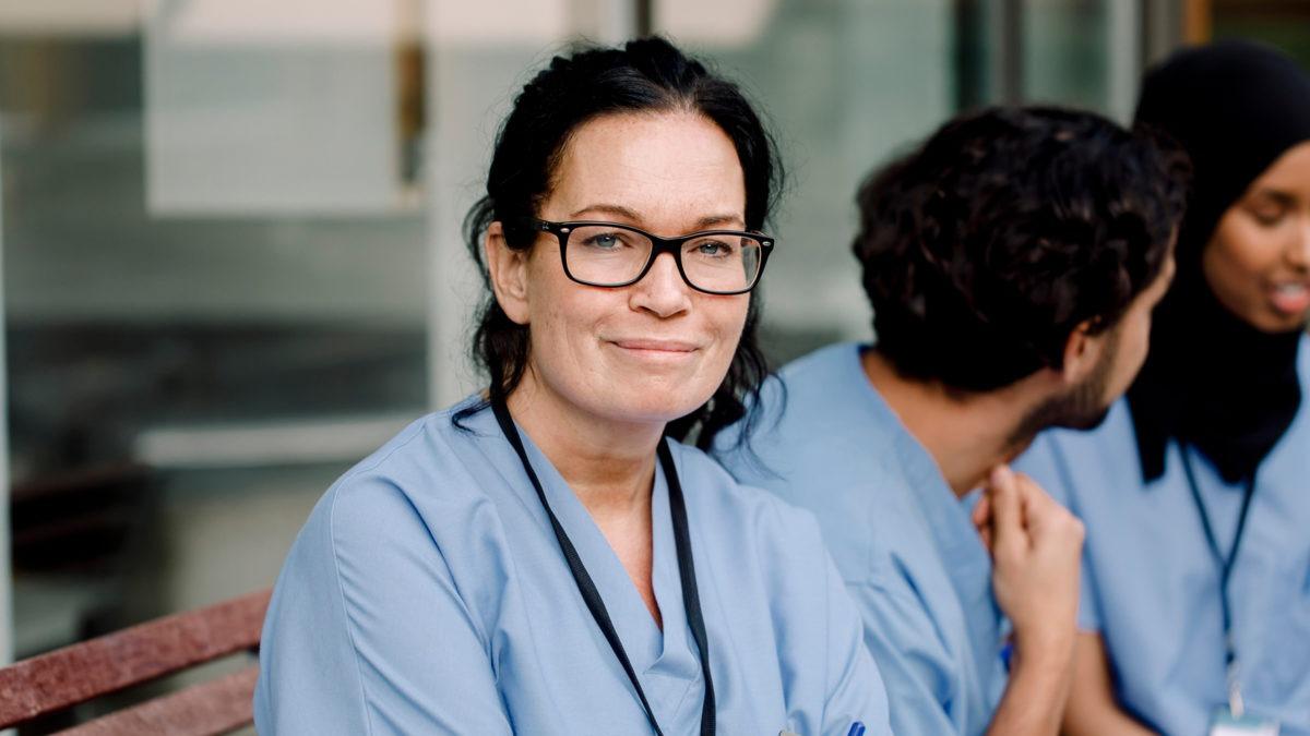Sjukvårdspersonal tar paus på en bänk utomhus