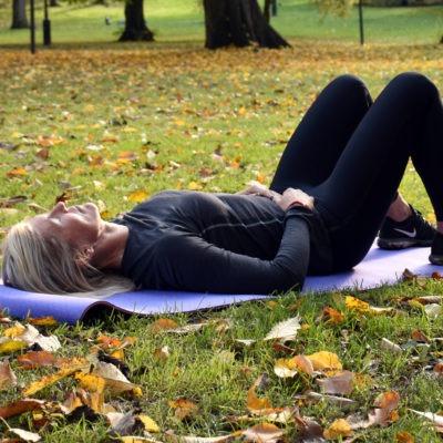 Träningsklädd vinna ligger på yogamatta på gräsmatta med höstlöv, tema utmattningssyndrom. stress