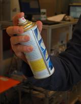 Hand som håller sprayburk med rengöringsmedel.