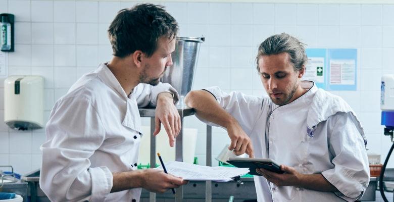 Två personer i ett storkök tittar på en checklista