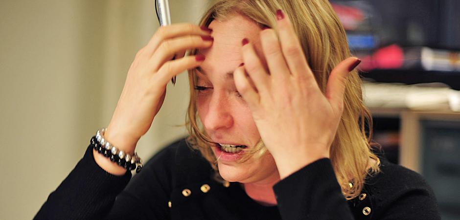 En kvinna håller händerna mot pannan i stress..