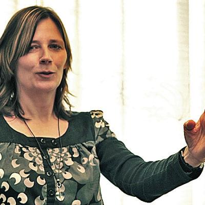 """En kvinna agerar ledare genom att peka """"med hela handen""""."""