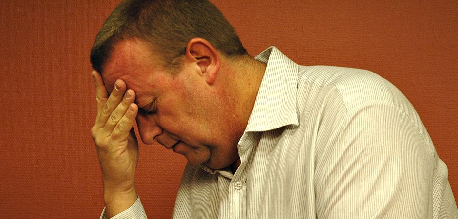 Medelålders man som lutar sig lätt framåt, med ena tummen och pekfingret mot näsroten för att visa att han är trött.
