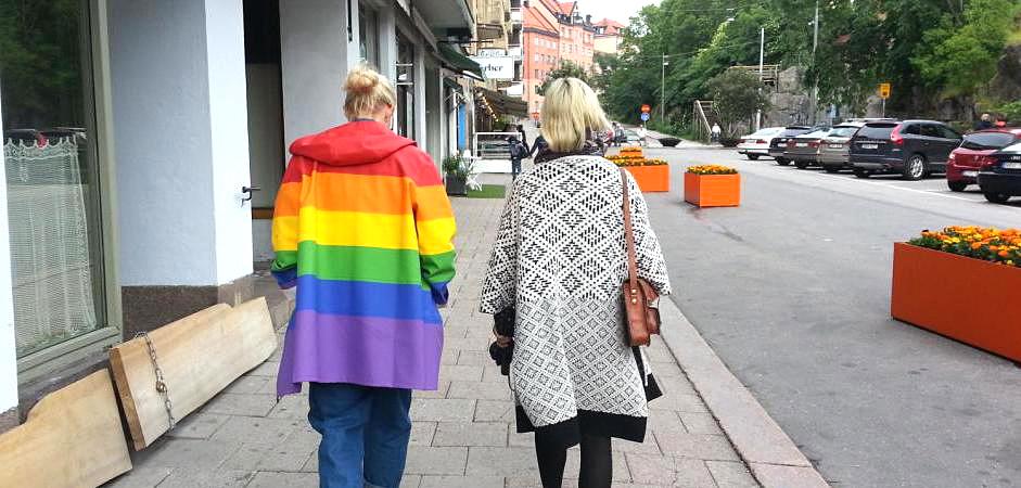 Foto på två personer som går med ryggen mot kameran. Den ena personen, till vänster, har en regnbågsfärgad regnkappa på sig.