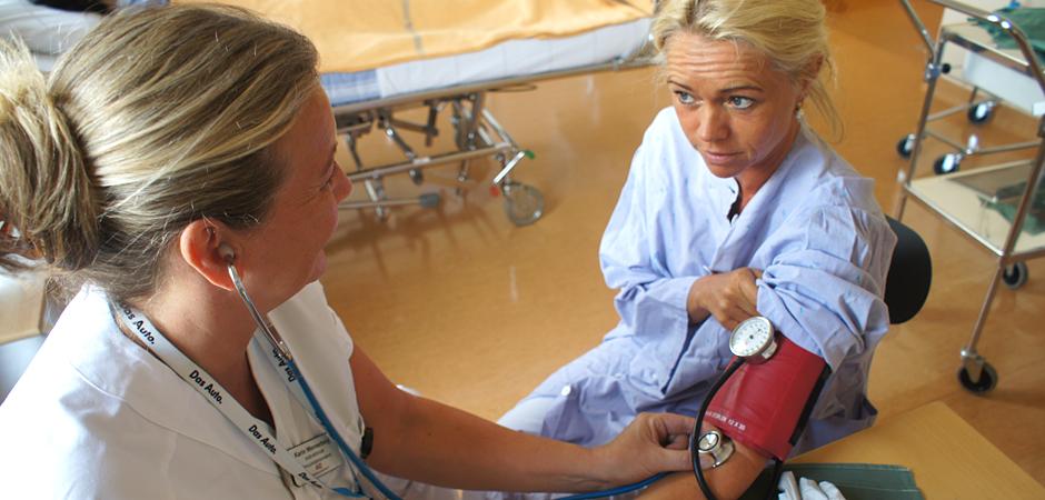Iscensatt bild av en sjuksköterska som tar sänkan på en kollega.