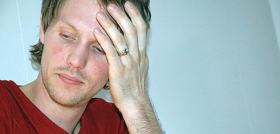 Närbild på ung man som sitter vid ett bord med blicken riktad nedåt och huvudet lutat i ena handen.