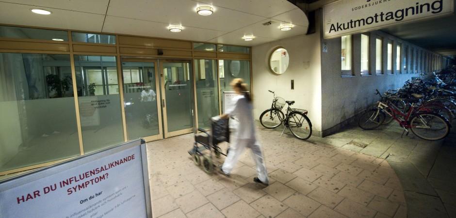 En sjuksköterska kör en rullstol in en sjukhusentré.
