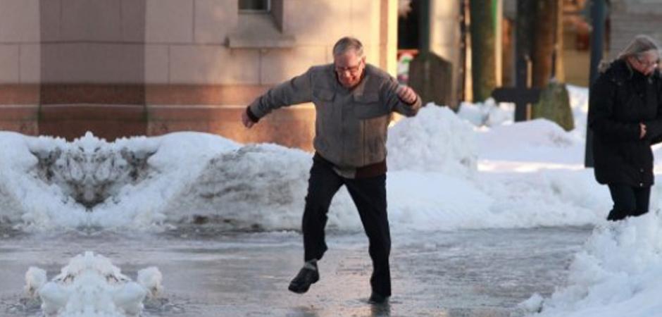En man halkar till på en isfläck.