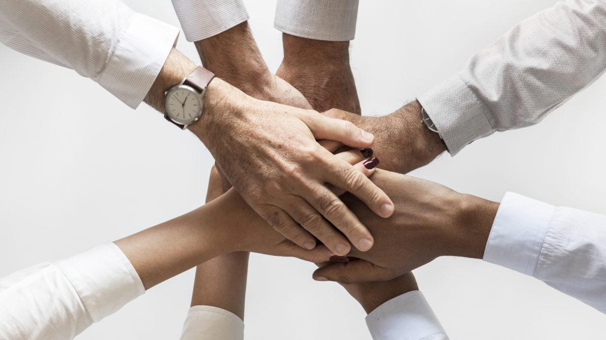 8 händer som ligger ovanpå varandra. vita skjortärmar syns också.