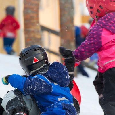 Barn som leker i en snöig backe