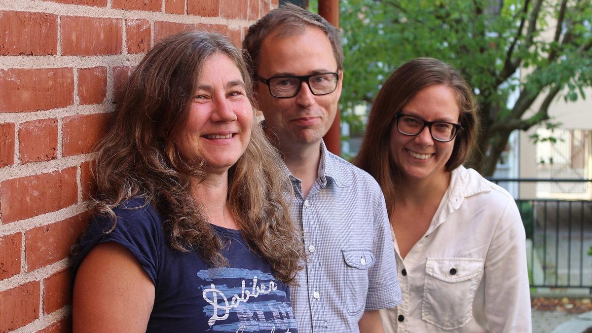 Tre personer som står och skrattar bredvid varandra