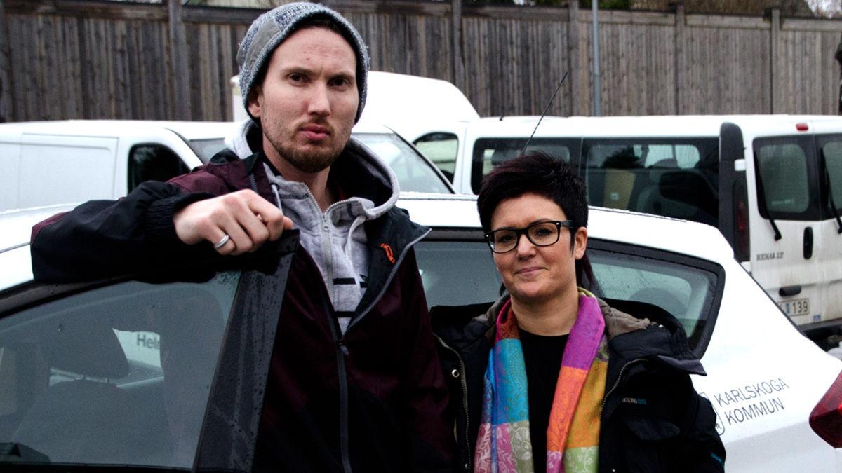 Niclas och Lotta står framför en bil med bildörren öppen