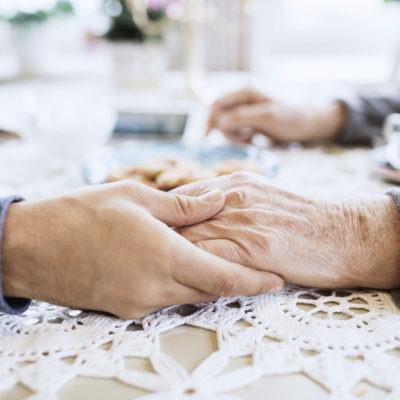 Vårdare tröstar äldre man vid matsalsbord