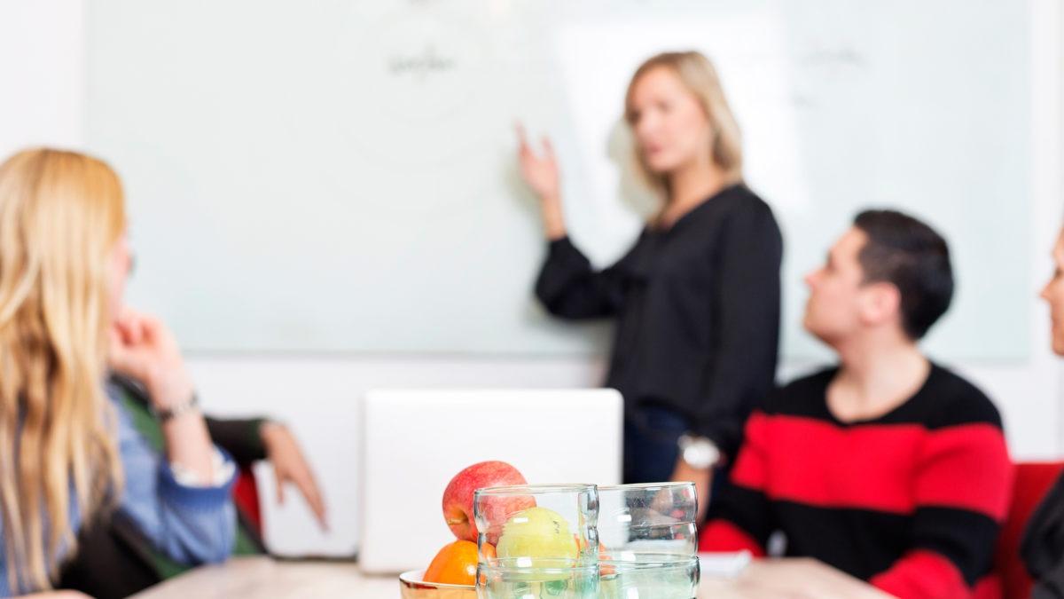kvinna står vid whiteboard och tre personer sitter vid ett bord.
