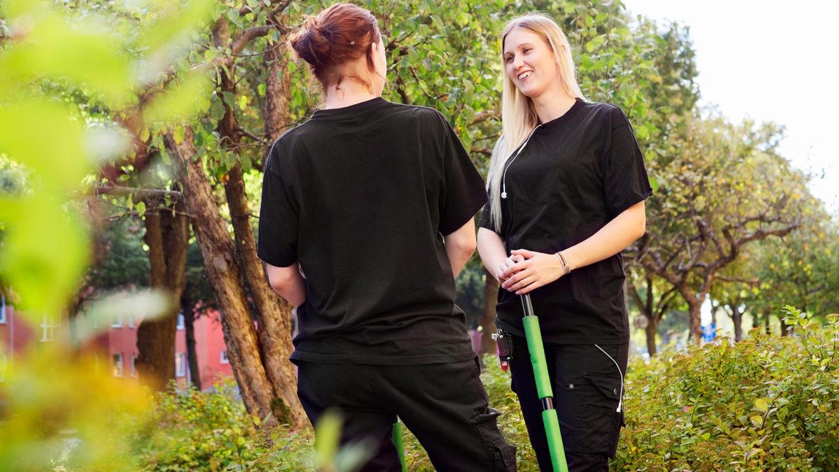 två unga kvinnliga parkarbetare pratar med varandra i grön park.