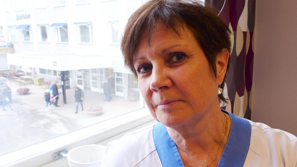 Mörkhårig Maria Raumer står vid ett fönster och tittar in i kameran