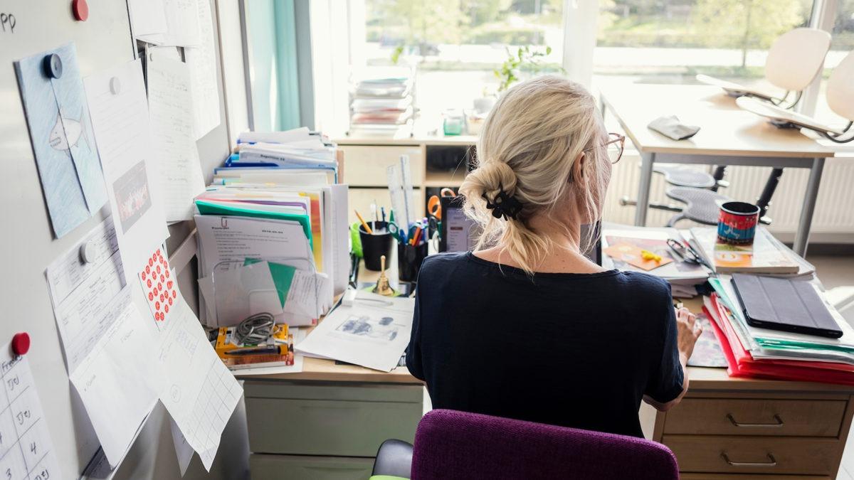 lärare vid skrivbord fotad med ryggen mot kameran