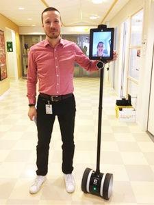 en man i en sjukhuskorrdior håller i en robot som består av en segway, samt en åinne med en ipad-skärm i ögonhöjd.