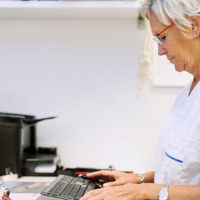 Läkare sitter vid skrivbord och skriver på dator, sedd i profil.