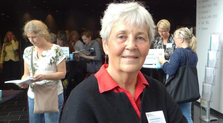Elisabeth Börjesson, rehabkoordinator, sedd framifrån i svart kofta med röd tulpan broderad. Kvinnor på konferens i bakgrunden.