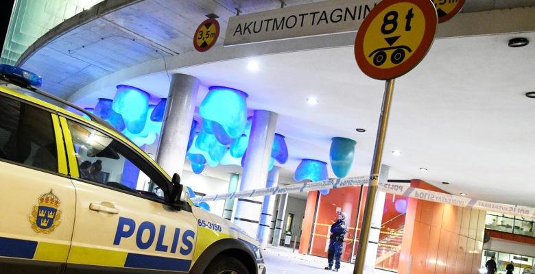 polisbil på väg in på akutmottagning. polis står och vaktar framför entrén.
