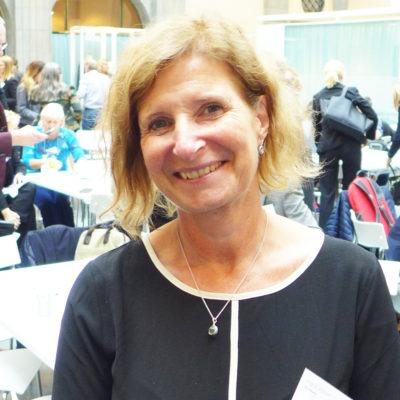 Ingrid Wibom, HR-chef i Botkyrka, ler in i kameran. Bakom henne syns personer som deltagit i regeringskonferensen om hållbart arbetsliv.