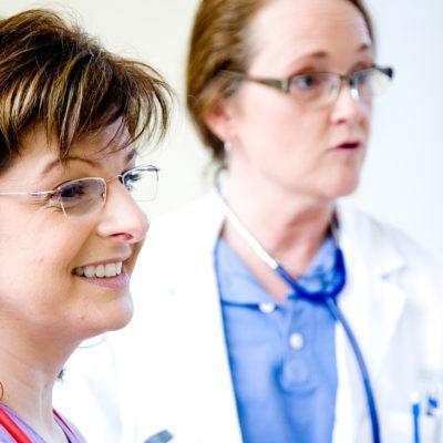 närbild på två kvinnliga läkare snett från sidan, i sjukhuskläder med stetoskop runt halsarna.