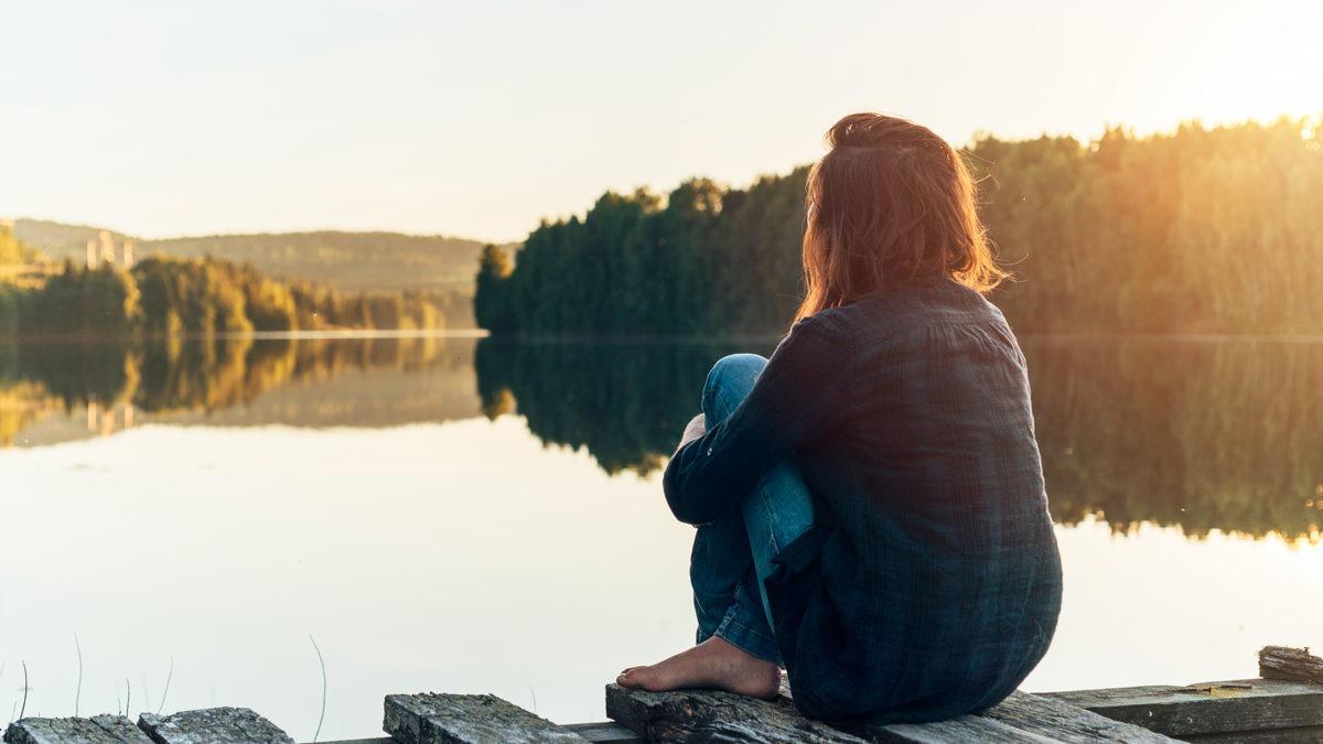 Kvinna sed bakiifrån sitter på brygga vid en blank sjö.