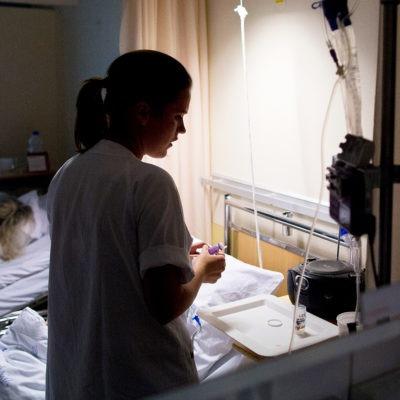 Vårdpersonal i nedsläckt vårdsal med sovande patient