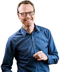 halvbild framifrån på Kirster Torssell i blå skjorta, leende och lite tillbakalutad