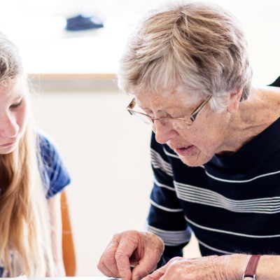 Äldre kvinna hjälper elev med textilarbete vid symaskin.Äldre kvinna hjälper elev med textilarbete vid symaskin.