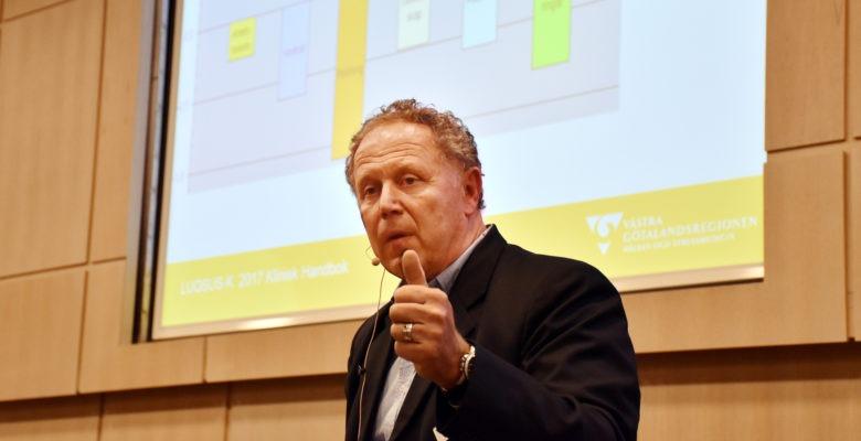 Artur Tenenbaum gör tummen upp framför diagram på stor skärm