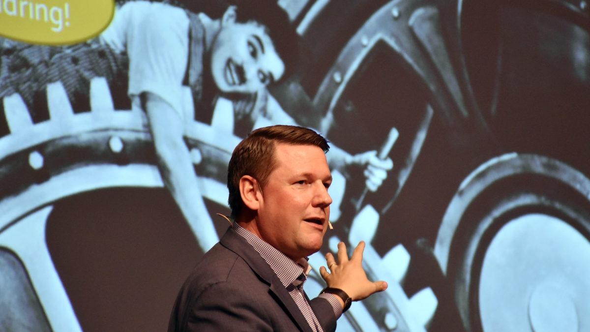 Bröstbild på Tobias Baudin som tittar och åt höger, står framför storskärm med bild på Chaplin ur filmen Moderna Tider