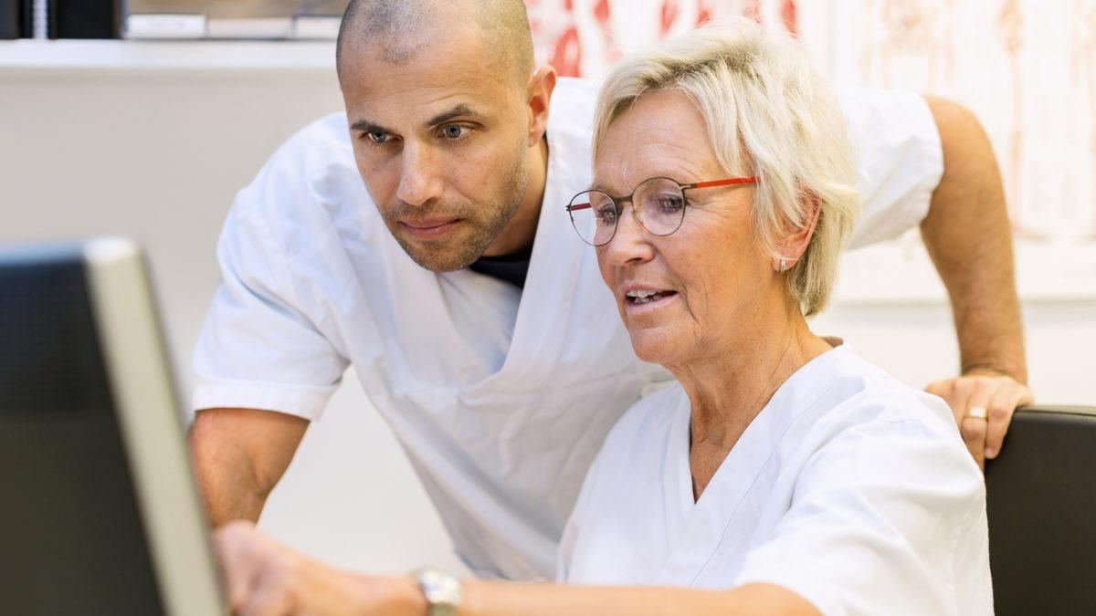 Sjukvårdspersonal en man en kvinna pekar och tittar på dator, IT i vården