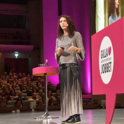 Forskaren Cecilia Berlin, klädd i lång kjol, talar till en stor publik från en scen på arbetsmiljökonferensen Gilla Jobbet