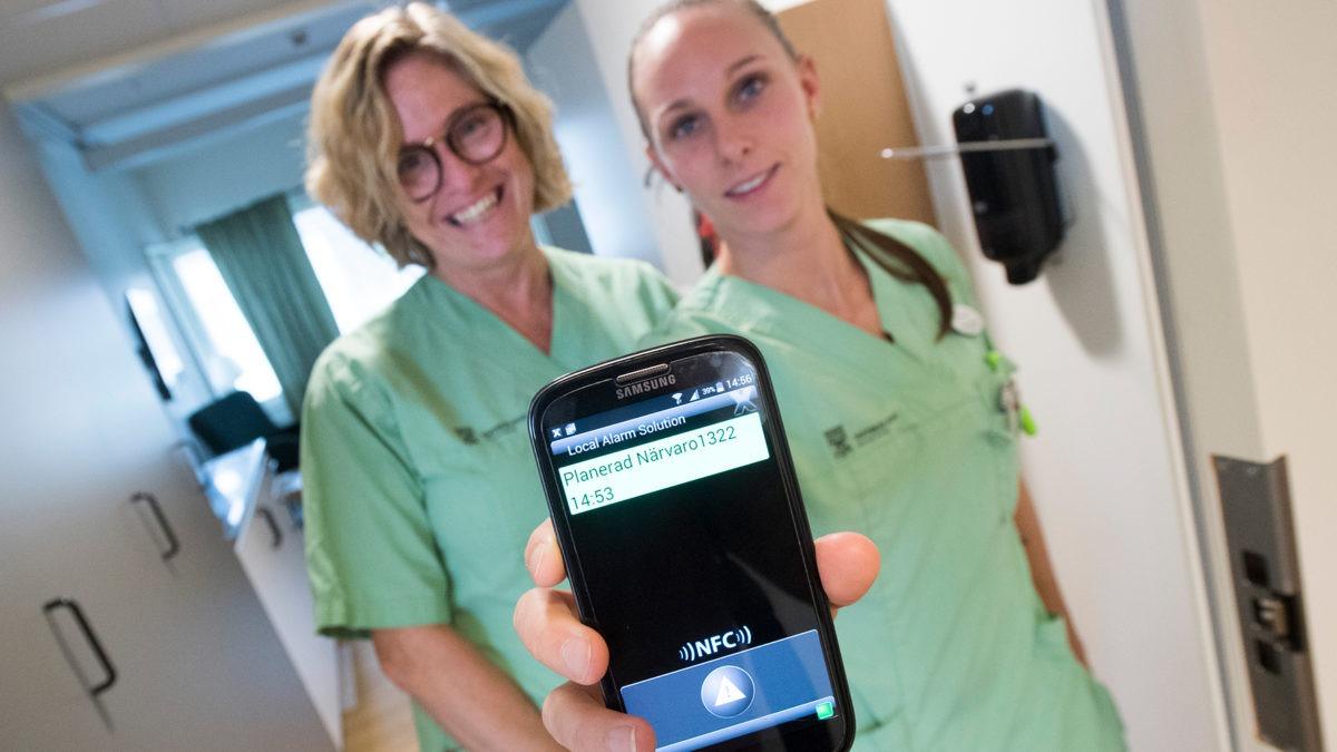 """två kvinnor i gröna sjukvårdskläder står tätt intill varandra i en korridor, och håller fram en mobil med texten """"Planerad närvaro""""."""