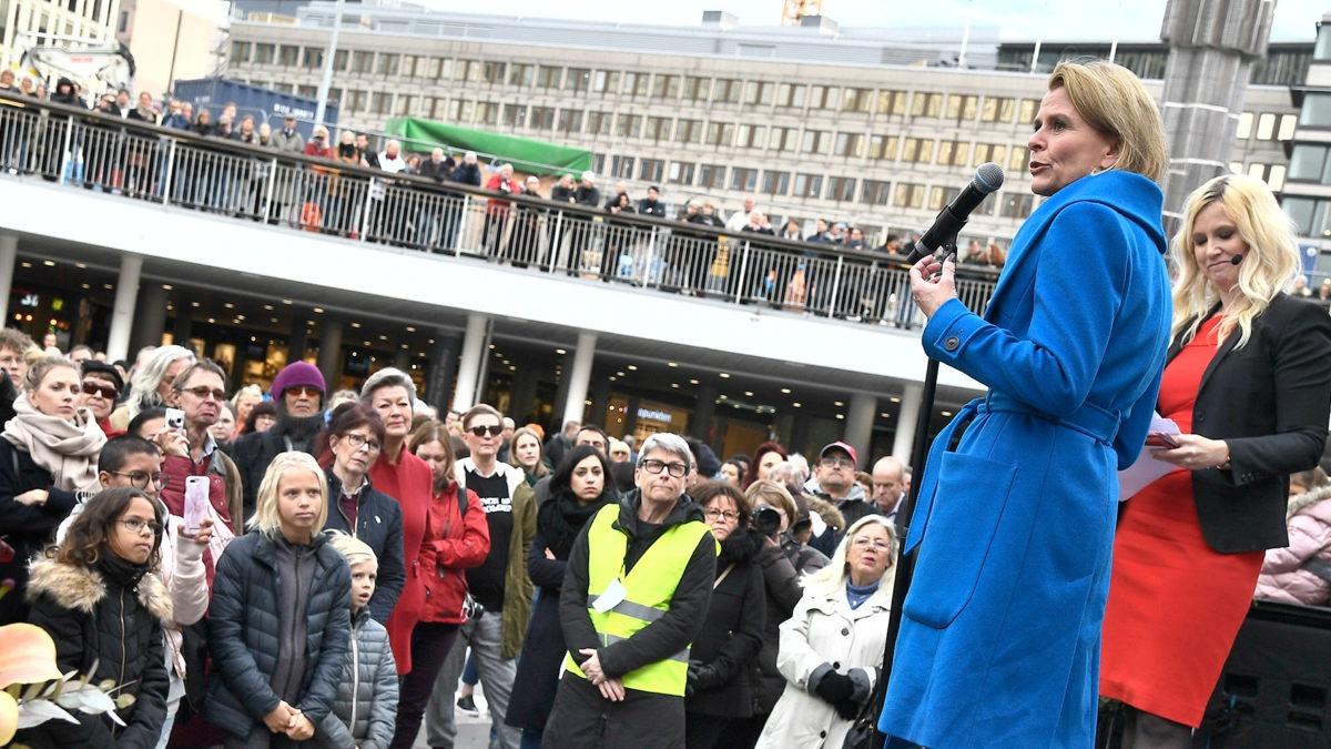 manifestation på¨sergels torg med jämställdhetsminsiter Åsa Regner i blå kappa i förgrunden, fotad snett nedifrån. publik med många barn och kvinnor framför scenen.