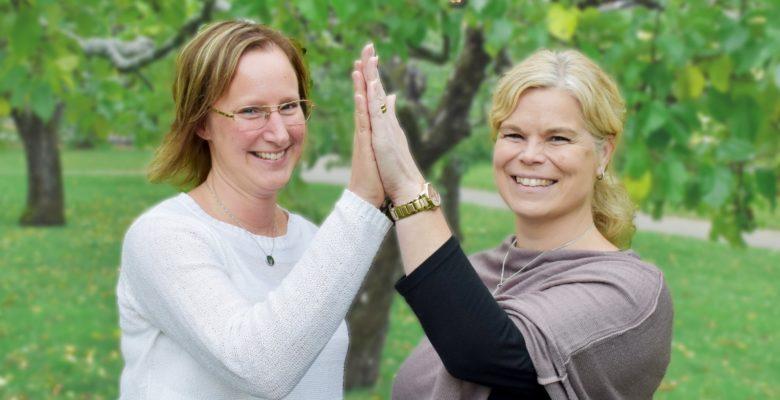 susanne persson och sofia johansson står på en gräsmatta och gör high five mot varandra. de är glada. susanne persson har en vit tröja, sofia johansson har en grå tröja.
