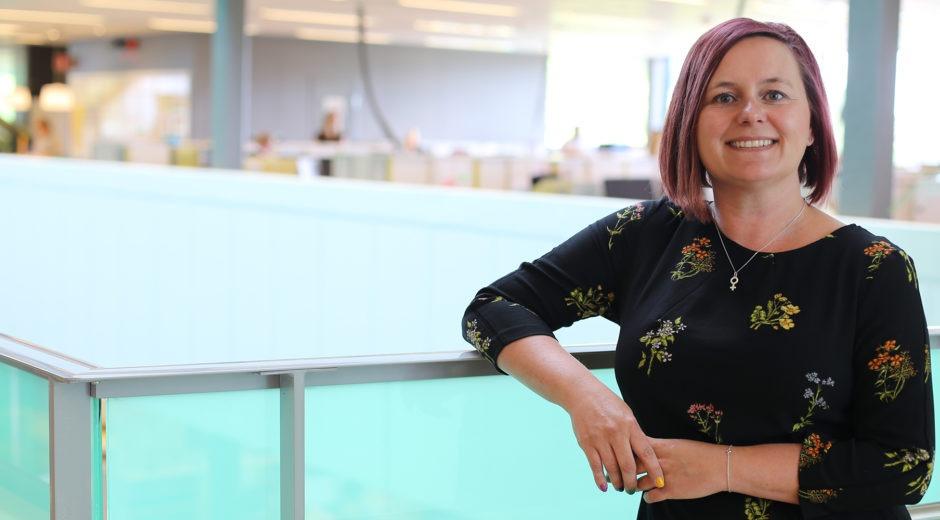 halvbild på sara Kvist Lindgren, projektledare för Hållbar hälsa. Hon har halvlångt rakt hår, ler och står lutad mot ett räcke i en officiell hall, ljus och grönmålad omgivning.