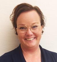 charlotte isoz, porträtt rakt framifrån, brunt bakåtstruket hår och stora ljusa glasögon, ser glad ut.