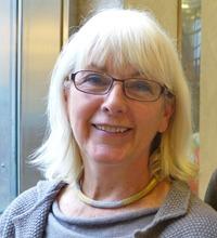 Eva Vingård porträtt tittar och ler in i kamera