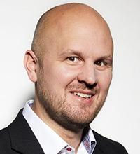 porträtt på glad Olof Ambjörn, skallig med lite skägg och vit skjorta och svart kavaj som syns vid halsen.
