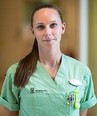 desiree westerberg i grön sjukhusskjorta med uppsatt brunt hår i hästasvans som hänger fram över axeln, ser rakt in i kameran.