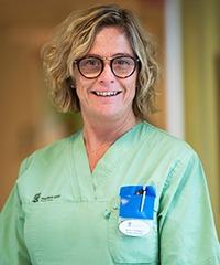 maria sandhagen, enhetschef på Hääleborgs äldreboende, i blont vågigt utsläptt hår och gröna sjukhuskläder. ler och ser in i kameran.