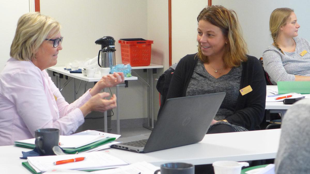 två kvinnor sitter vid ett bord och pratar. kvinnan till vänster i rosa skjorta gestikulerar, kvinnan till höger i svart kofta ler och lyssnar. En tredje kvinnan i vit tröja syns till höger bortom de andra två.
