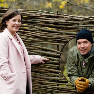 porträtt på Linda Corin, i rosa kappa, och Martin Levin, i grön jacka och svart mössa, som tittar ut genom ett hål i ett staket. Båda ser glada ut. De har båda jobbat med en medarbetarenkät i Västra Götaland.