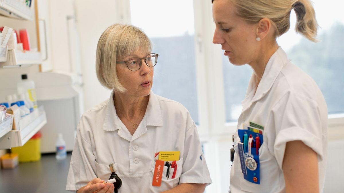 Apotekare Gerd Petersson visar sjuksköterska Ulrika Alegrievski något framför en läkemedelshylla