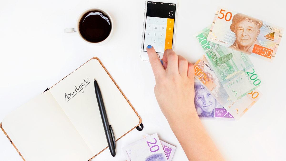 arrangerad bild mot vit bakgrund med pengar, en hand som pekar på en miniräknare, ett anteckningsblock och en kopp kaffe. Allt sett ovanifrån.