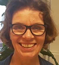 ingela målqvist, en glad kvinna med brunt hår och galsögon ler stort in i kameran.